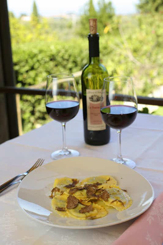 Piatto tipico di ravioli al tartufo di San Miniato accompagnati da un bicchiere di vino.