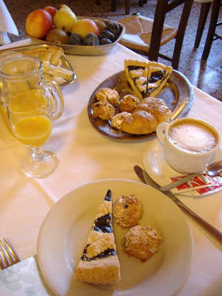 Colazione continentale completa con torta, cappuccino, the, succo di frutta e yogurt.
